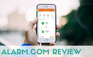 Personal holding phone with Alarm dot com on screen (caption: Alarm.com Review)
