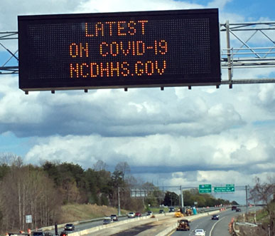 COVID-19 highway alert in north carolina on interstate (alert reads: latest on COVID-19 NCDHHS.gov)
