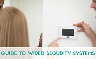 Lady with ADT keypad and installer (caption: Guide to Wired Security Systems)