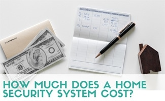 Desk with money, finances and home block (caption: How Much Does A Home Security System Cost?)