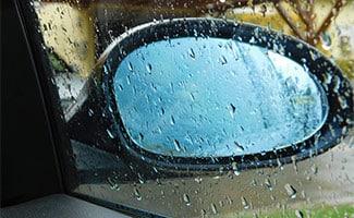 Car door window with mirror in rain