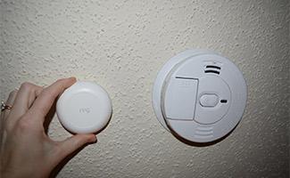 Hand placing a Ring Alarm Smoke & CO Listener