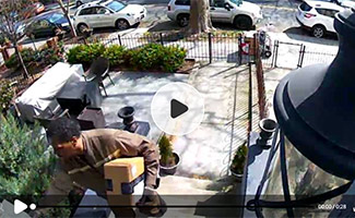 Postman delivering package on security camera