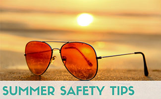 Sunglasses next to beach in sun (caption: Summer Safety Tips)