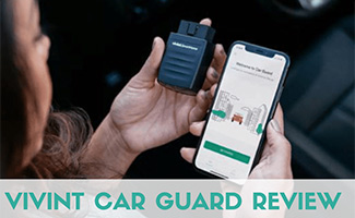 Woman holding phone and car guard (caption: Vivint Car Guard Review)