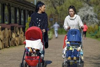 Two women walking kids in strollers from a distance